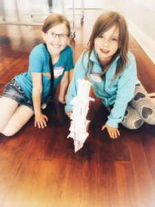 Two girls making towers our of paper, paperclips and tape at Bricker-Price Block's Kid's Club.